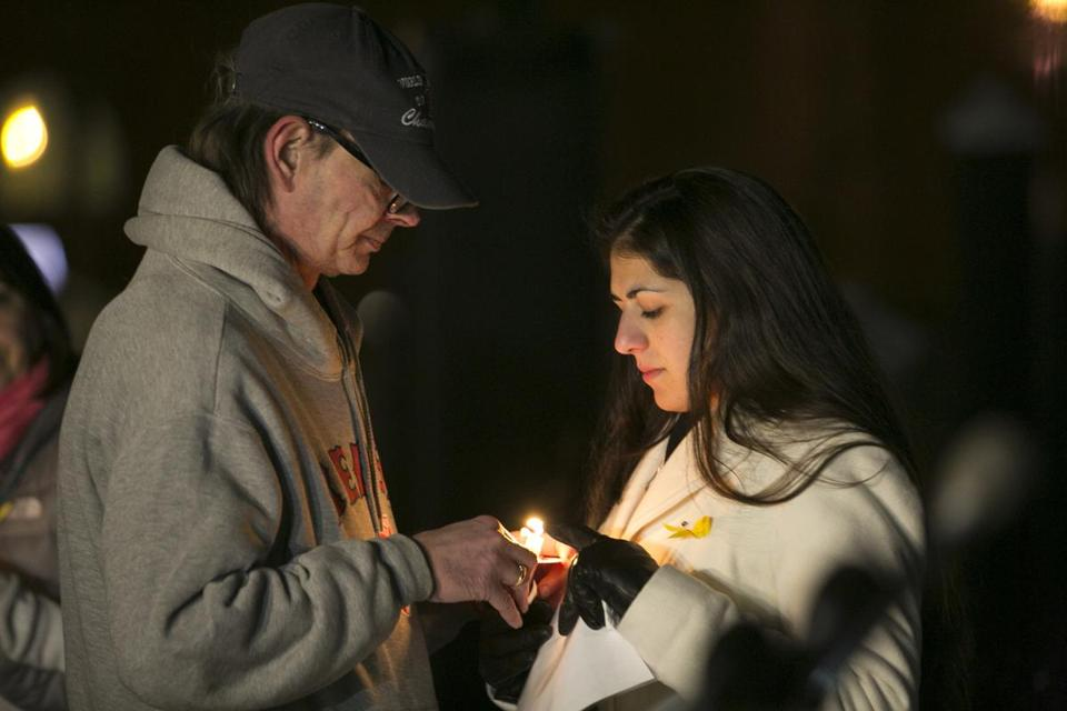 Keith Munsell lit a candle for Allison Bitto at a vigil for his son Eric Munsell, who disappeared three weeks ago. Others at the vigil in Boston on Saturday held signs with photos of Eric.